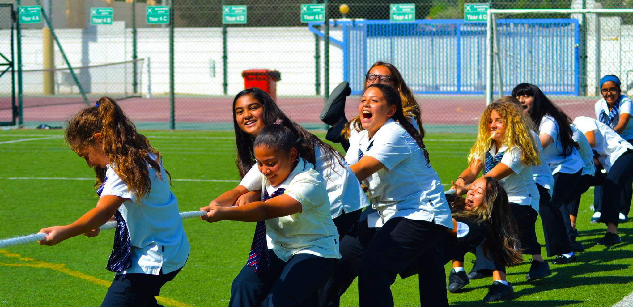 Sporting photograph of girls at GEMS Wellington International Dubai competing in a Tug of War competition