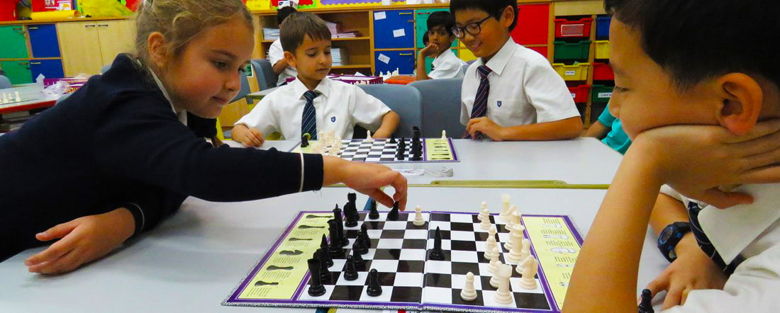 Photograph of enthralled children at GEMS wellington International School in Dubai playing chess