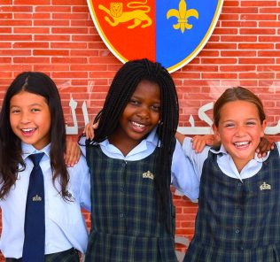 Photograph showing students at Kings' School Al Brasha undder the school's coat of arms