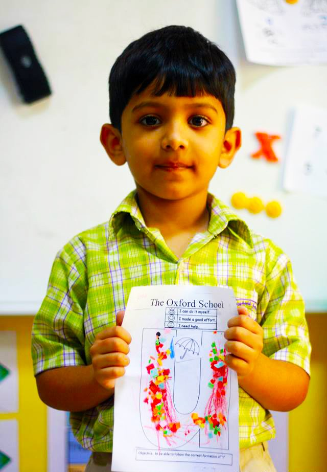 A young child at the Oxford School Dubai showing pride in his work