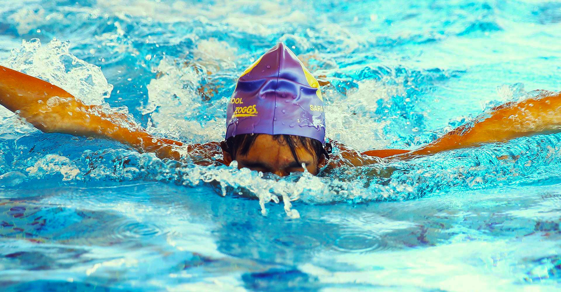 A photograph of a child competing in swimming at Safa Community School in Dubai