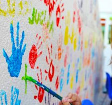 An image of a young girl with a paintbrush at GEMS Wellington Primary School in Dubai